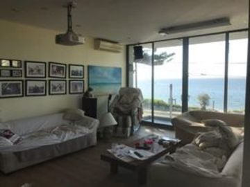 Renting out with online payment: Living Room with Large Windows and Waterfront Views